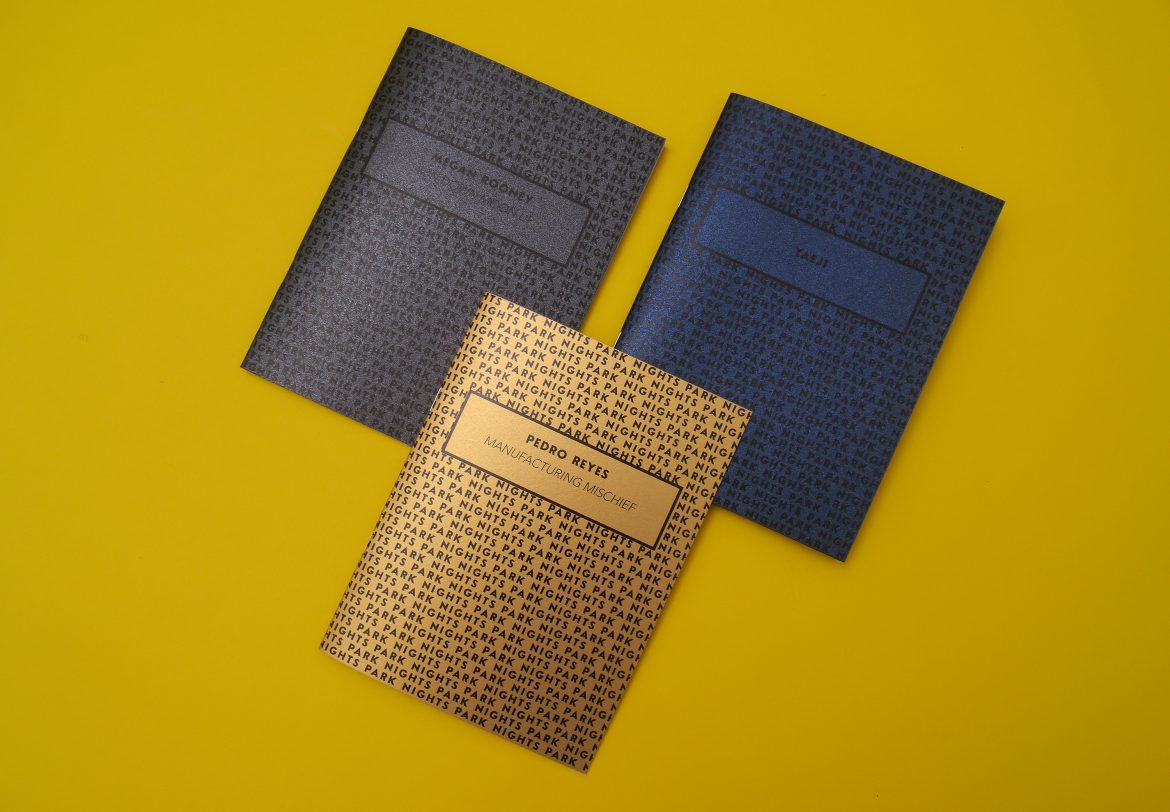 Three Park Nights programmes with metallic covers in gold, navy blue, and charcoal