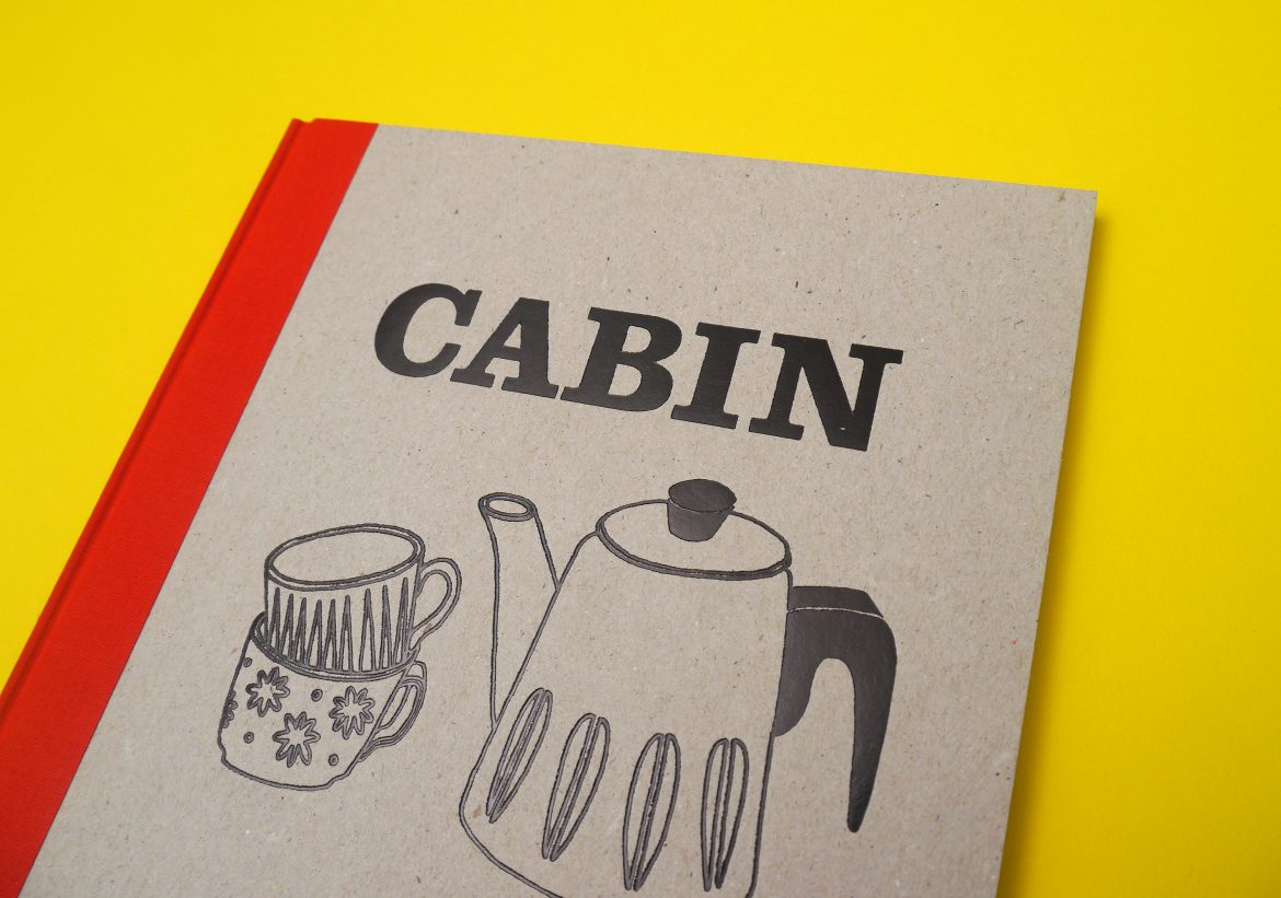 Hardback book with a cardboard cover and red spine against a yellow background, the title in black reads Cabin, with an illustration of a coffee pot and two cups